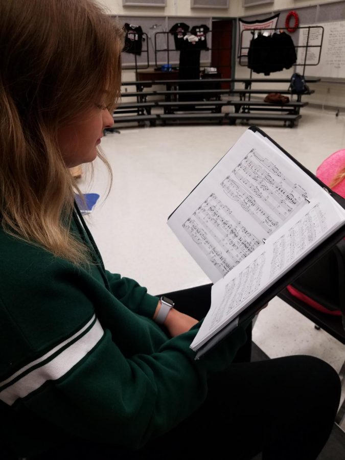 Singing For Others Senior student, Molly Berry, reads over her music in hopes of helping other choir classmates understand the new Christmas music given to them.