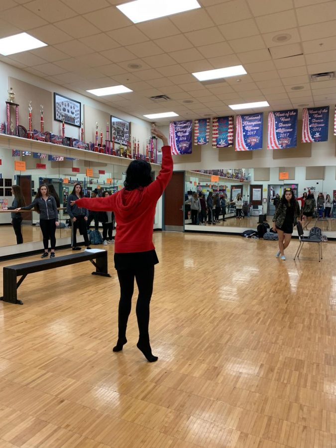 When in doubt... dance! Anna Blair teaches her Dance II class the aspects of ballet. Here, she demonstrates a plie to her students whom are using the barre (bar)  to practice their skills.