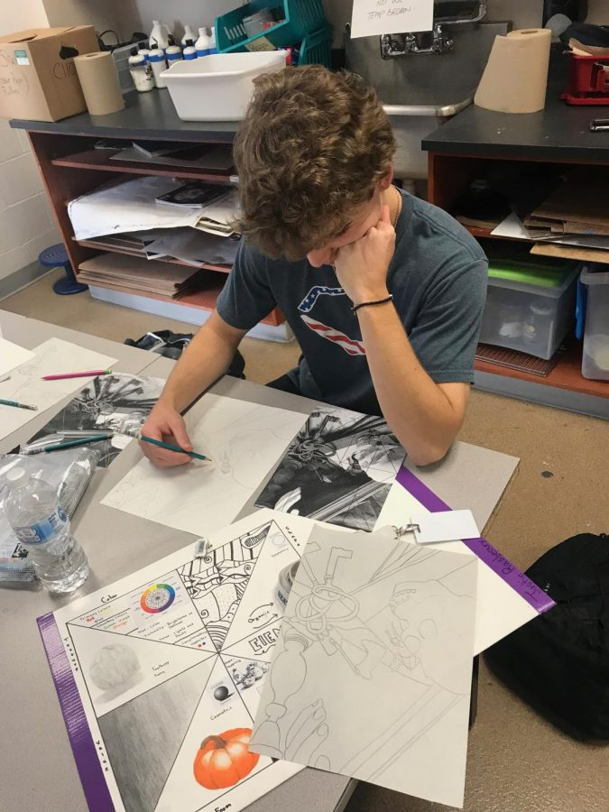 Picasso? Junior, Justin Rasbeary, channels his inner artist and sketches out a drawing for his art class.