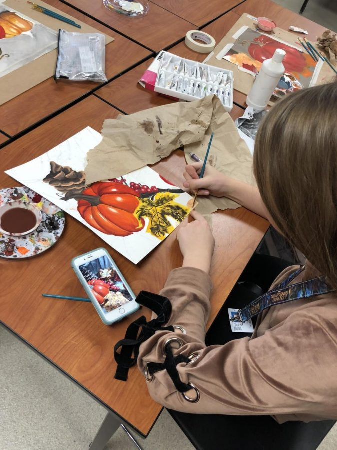 Pumpkin Painting Alley Wiprud painting a Thanksgiving scene in Art 2. This shows that Heath is contributing to the holiday season while incorporating it into their work.
