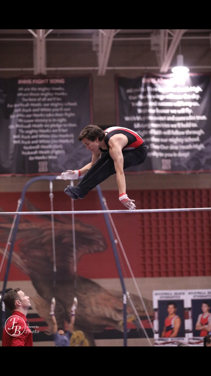 Travis Irizarry performing a flight on the high bar during state championship last year.