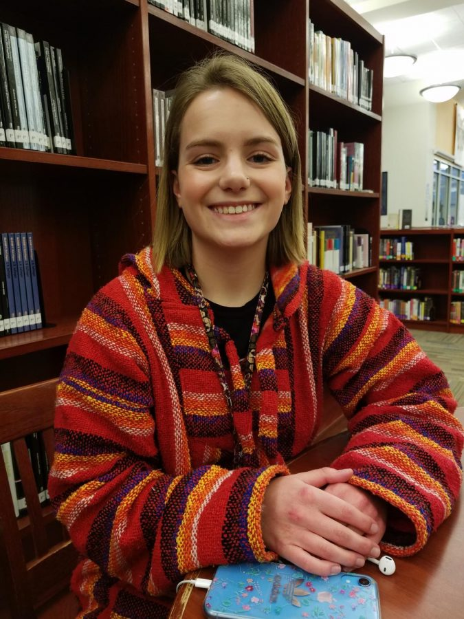 """Not your ordinary girl // Isabella Maxcey, junior, catches up on reading a good book while listening to music. """"Most people don't really know that I'm in fashion,"""" said Isabella. Isabella breaks social boundaries through fashion designs and athletics."""